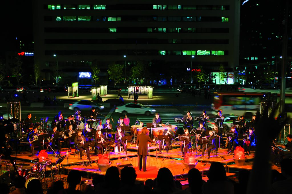 SEOUL, KOREA - SEPTEMBER 23, 2009: A full symphany orchestra plays music on a sidewalk near downtown traffic at a free summer night concert series on September 23, 2009 in Seoul, Korea